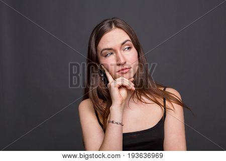 Beautiful young woman with a sly look portrait. Thoughtful girl looking away and planning something, dark background