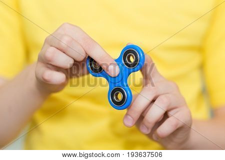 A boy is playing a popular toy fidget spinner in his hands. Stress relief. Anti stress and relaxation fidgets spinner for tired people. Boy playing with a fidget spinner.