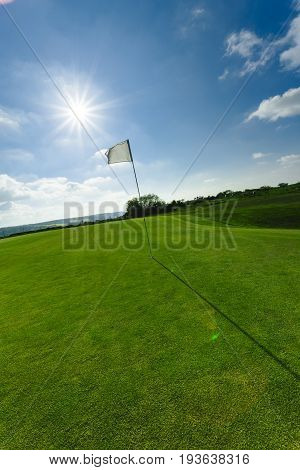 View Of A Green Golf Course, Hole And Flag On A Bright Sunny Day. Sport, Relax, Recreation And Leisu