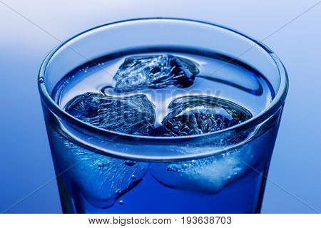 Deep blue colored drink with ice close up. On abstract blue background.