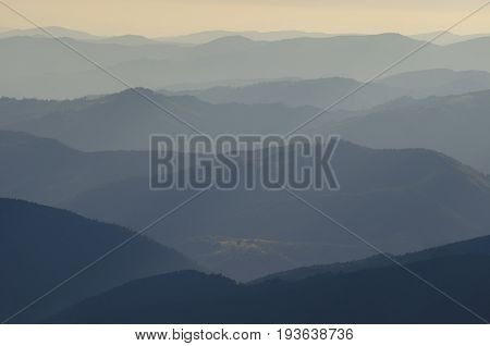 Sunlit mountains ranges. Evening or morning scene. Yellow meadow in the composition middle.