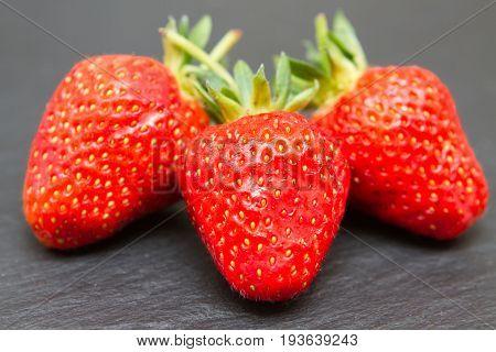 A closeup of three ripe summer strawberries