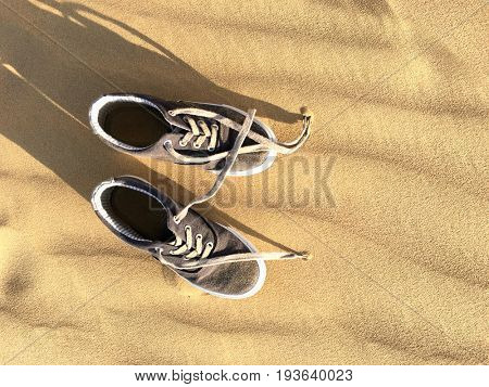 Pair of young kid's shoe laying on a dessert sand on a hot sun. View from above.