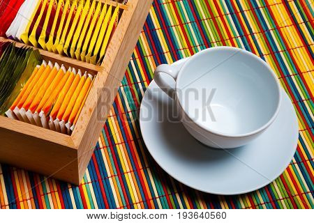 Tea cup and bags. An empty cup and a wooden box with inside some bags of tea. Background colorful to strips of wood. High definition.