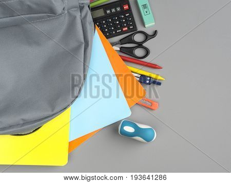 Top view of a backpack and school supplies on grey background
