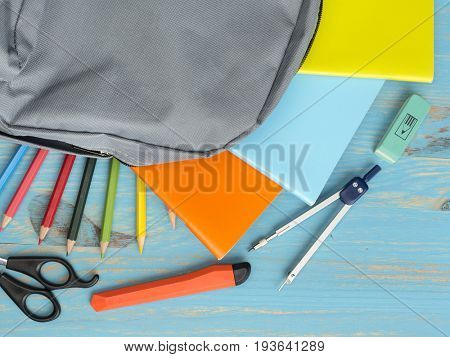School backpack and supplies on table background