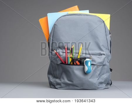 Backpack with school supplies on grey wooden table