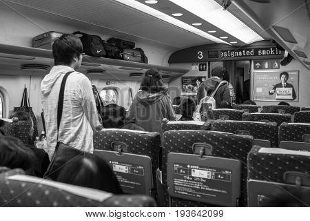 KYOTO, JAPAN - NOVEMBER 12, 2016: People inside the Shinkansen train on the way to Tokyo, Japan. Shinkansen is a network of high-speed railway lines in Japan.