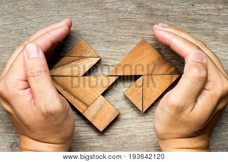 Wooden tangram puzzle in separate heart shape background (Concept for love complete care for the broken relationship)