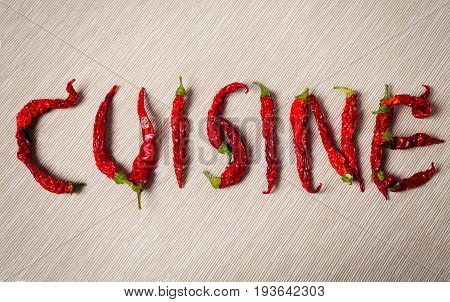 Cuisine. Word with dry red hot chili pepper. Composition of the word food with dried chillies. Diagonal striped fabric background.