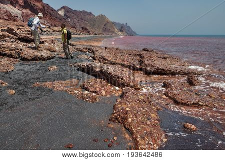 Hormuz Island Hormozgan Province Iran - 17 april 2017: Iranian Island of Hormuz in Persian Gulf tourists are photographed on the red beach using a smartphone.