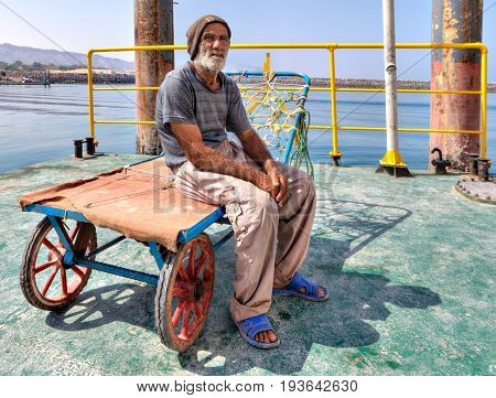Hormuz Island Hormozgan Province Iran - 17 april 2017: One elderly Iranian port loader sits on his trolley on the pier of the island of Ormuz.
