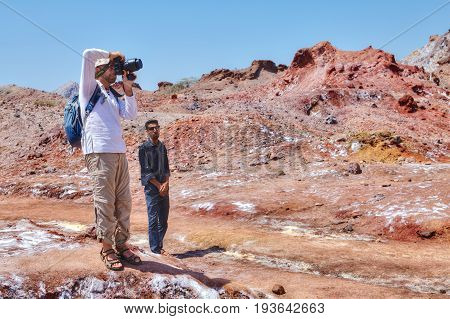 Hormuz Island Hormozgan Province Iran - 17 april 2017: Iranian Island of Hormuz in Persian Gulf the guide is watching a tourist who takes photos of salt glaciers in salt mountains.