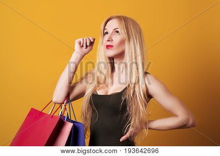 Young Blondy Girl Holding Shopping Bags Isolated Over Yellow Background.