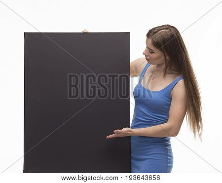 Young pry woman portrait of a confident businesswoman showing presentation, pointing paper placard black background. Ideal for banners, registration forms, presentation, landings, presenting concept.