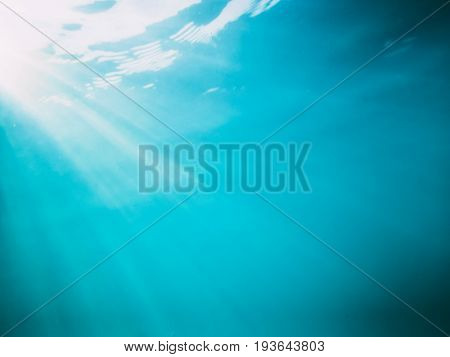 Wave underwater and sun rays. Blue ocean in underwater