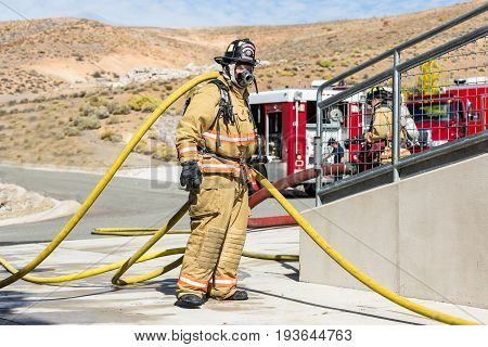 Firefighter Training Entering A Building With A Charged Hose