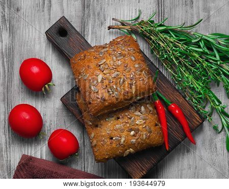 Whole grain fresh cereals bread buns with sunflower Sesame linen seeds. Spices for grain cereals bread buns tomatoes peppers rosemary thyme. Light white wooden background.Top view.