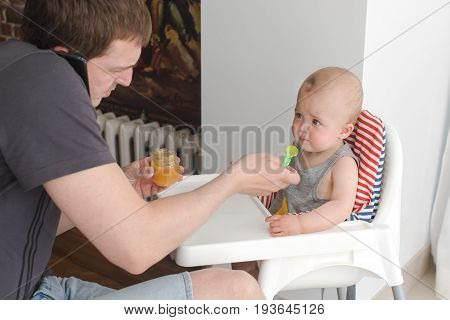 Dad feeds his son with fruit puree while talking on the phone and working. Careful father feeding little boy sitting in child chair.