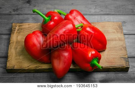 Heap Fresh red Bulgarian pepper on a gray rustic wooden background. Cutting board for red bell pepper.