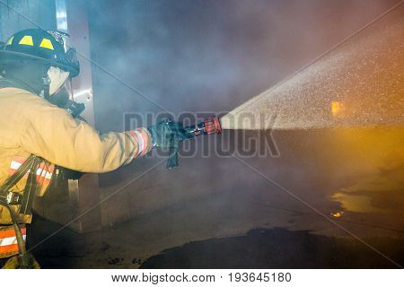 Firefighter Training Using A Hose To Put Out A Fire