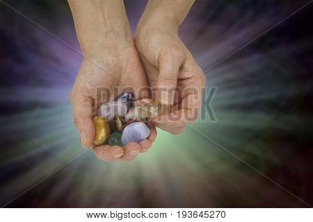 Crystal healing therapist holding selection of chakra colored crystals in cupped hand on a multicolored vignette light burst   background