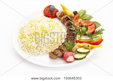 Grilled minced meat lamb skewer served with rice and herb on a plain plate. Fusion food concept and Persian traditional kebab koobideh or kubide. High angle studio shot on white background. Closeup.
