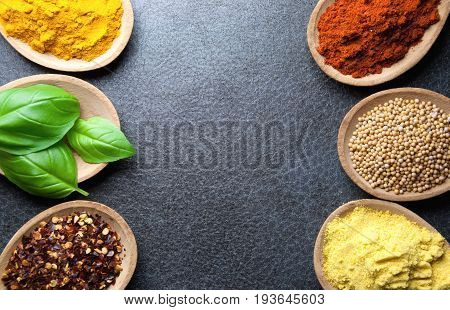 Closeup of herbs and spices in wooden spoons on a kitchen worktop background
