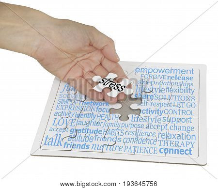Stress Management Puzzle Word Cloud -  a hand holding the final jigsaw piece over a jigsaw puzzle  showing a word cloud containing words relevant to stress management