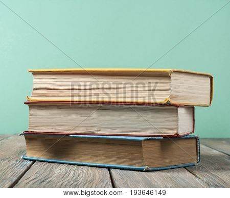 Colorful books on the table against the background of green wall. Back to school. Copy space for text. Education concept.