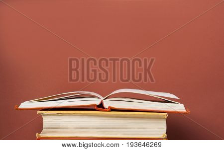 Open book, hardback books on the table on the background of red wall. Copy space for text. Back to school. Education concept.