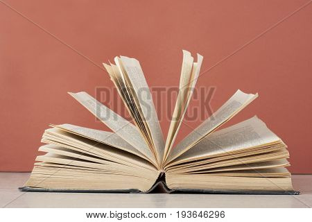 Open book on wooden table on red background. Back to school. Education concept.