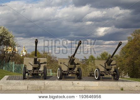 Three soviet anti-tank guns M-42 in a row at Kiev World War II museum in front of beautiful sky and golden domes of a church