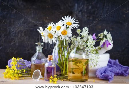 Mortar with fresh wild flowers and essential oil in glass bottles. Herbal medicine.