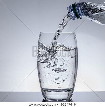 Wasser in das Glas einfüllen aus Flasche