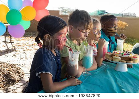 Happy children with face paint enjoying food and drinks at park