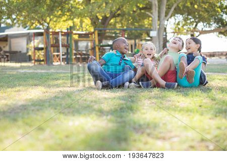 Cheerful children with arms around sitting on grassy field at park