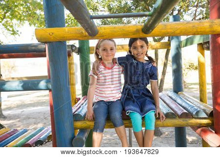 Portrait of smiling girls with arms around sitting on jungle gym at playground