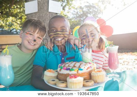 Portrait of happy children with face paint having food and drinks at park