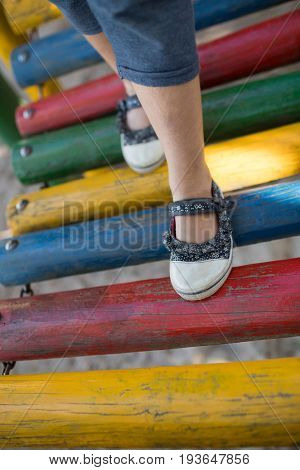 High angle low section of girl walking on jungle gym