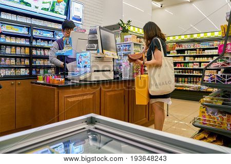 SEOUL, SOUTH KOREA - CIRCA MAY, 2017: woman paying at CU convenience store. CU is a convenience store franchise chain in South Korea.
