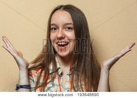 Emotional Portrait Of Happy Young Cute White Girl In Plaid Shirt Opposite Sienna Background.