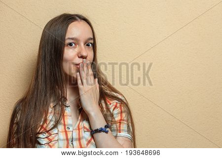 Emotional Portrait Of Surprised Young Cute White Girl In Plaid Shirt Opposite Sienna Background.