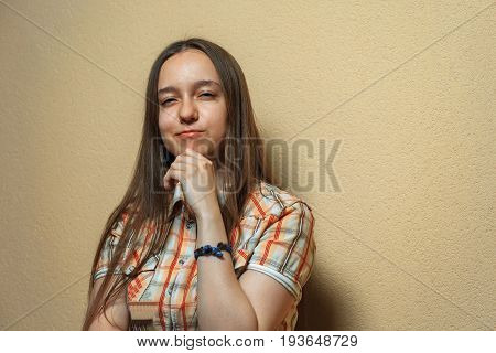 Emotional Portrait Of Pensive Young Cute White Girl In Plaid Shirt Opposite Sienna Background.