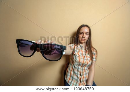 Emotional Portrait Of Young Cute White Girl In Plaid Shirt With Sunglasses Opposite Sienna Backgroun