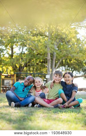 Portrait of cheerful children with arms around sitting on grassy field at park