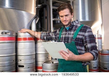 Worker reading while standing by kegs at factory