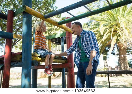 Happy father talking to son sitting on jungle gym at playground