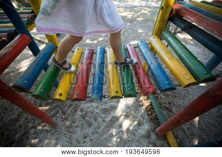 Low section of girl walking on jungle gym at playground