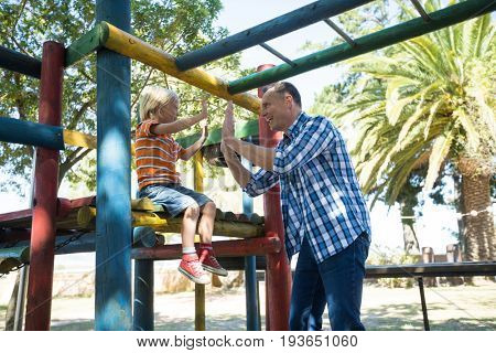 Happy father giving high five to son sititng on jungle gym at playground